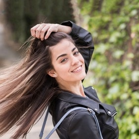 Model wearing a black jacket whipping her long straight hair over her shoulder.