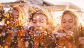 a group of girls having fun, blowing glitter